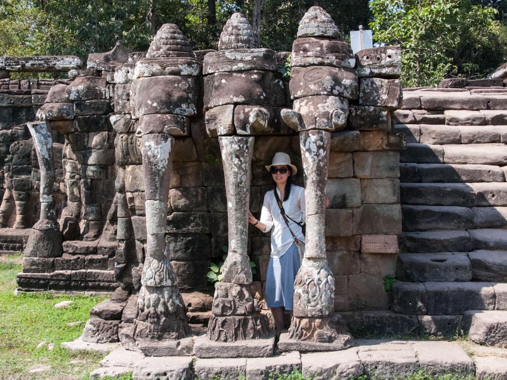 Sonya standing behind elephant trunks