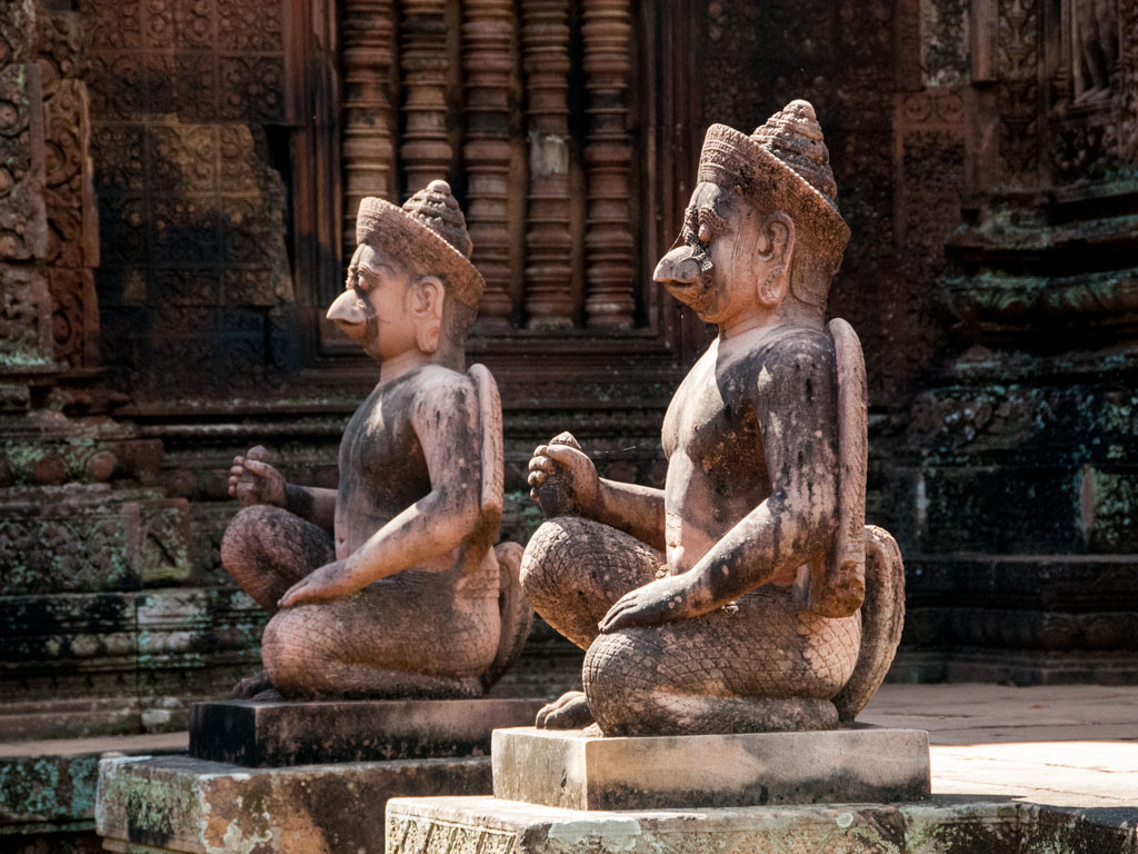 Guarded by two kneeling statues of human figures with animal heads