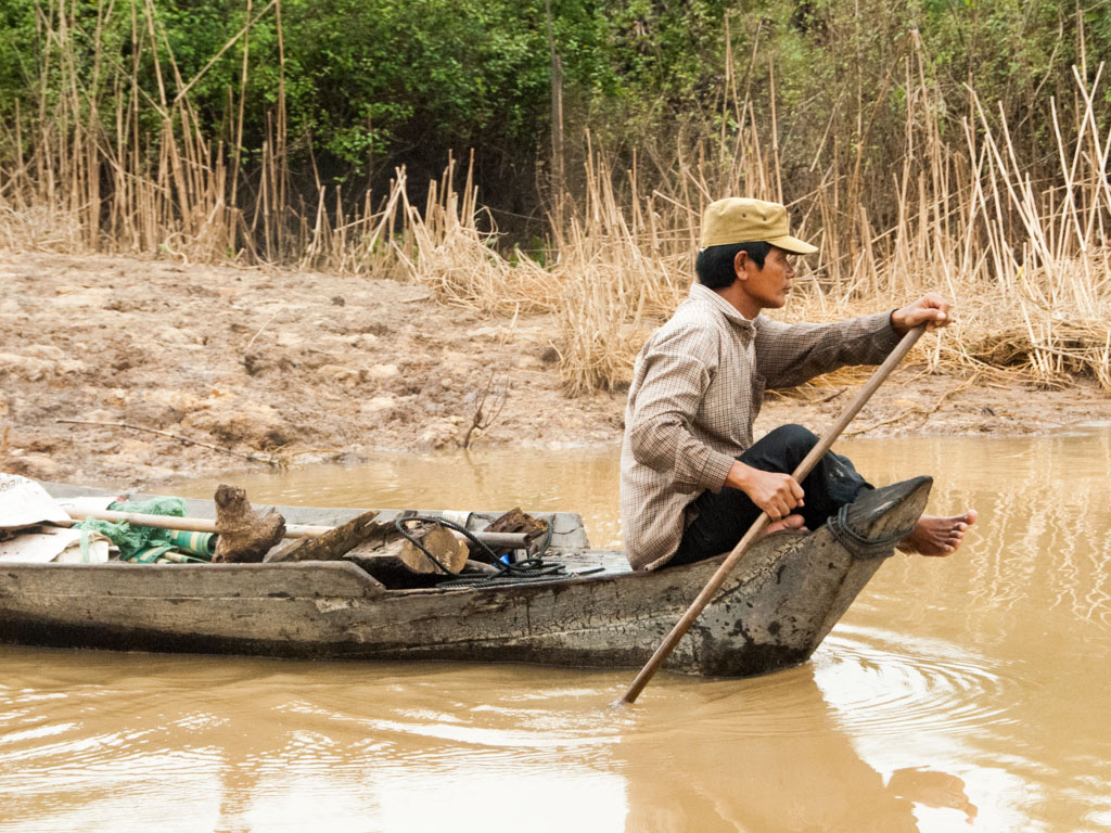 Man paddling wooden boat