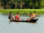 Waving children on a wooden boat