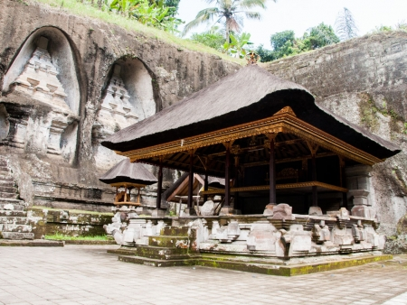 Under covered temple with rock-cut candi (shrines) in background