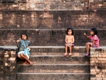 Cambodian girls sitting at the base of Kravan Temple