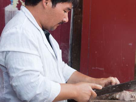Uighur man slicing goat meat