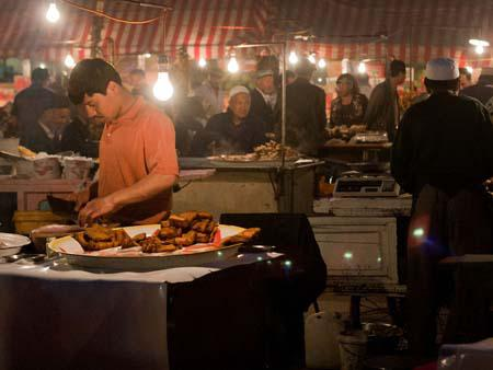 Uighur man slicing fried fish at the night market