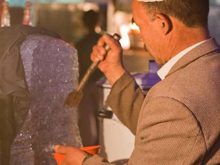 Uighur man shaving ice for dessert durap