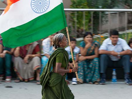 Elderly Indian women running with an Indian flag