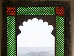 Colourful stain glass windows with Lake Pichola outside