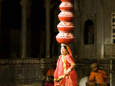 Woman balanced a staggering ten pots on her head