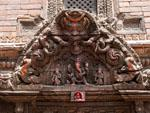 Intricately carved wooden windows, a Ganesh is seen above the entrance