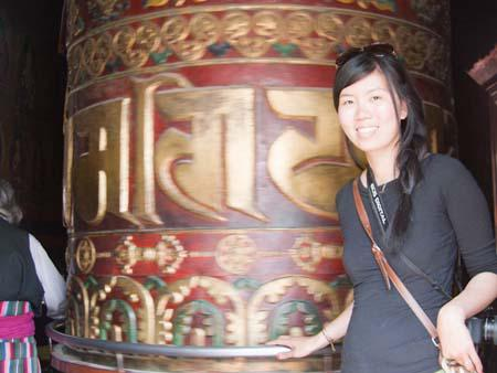 Sonya turning an extremely large prayer wheel