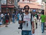 DSLR camera, GPS, Lonely Planet, backpack, Travis' blending in well