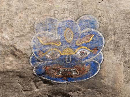 A monkey mask painting on a stone leading to the temple