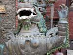 Metal snow lion at the entrance to a small Buddhist monastery