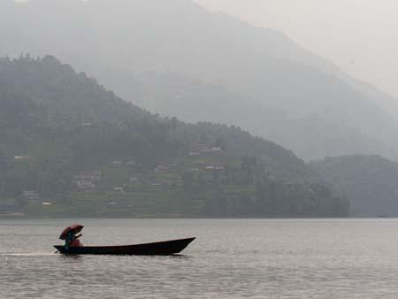 A lone Nepalese with canoe on Lake Phewa Tal