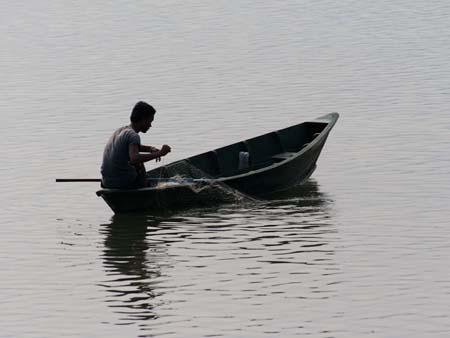 A man with a fishing net on Lake Phewa Tal