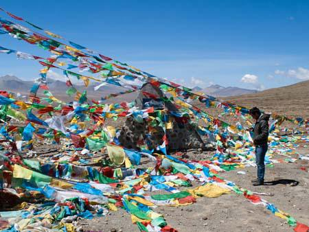 Elevation marker hidden between rows of prayer flags, Travis is checking GPS elevation