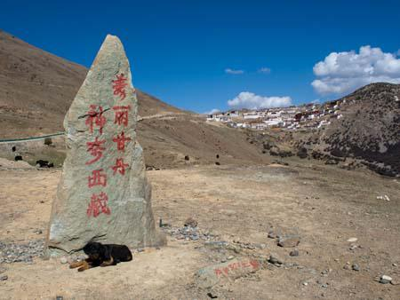 The Ganden Monastery sign with views of the monastery