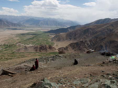 A sky burial site, a fire to the right and few monks