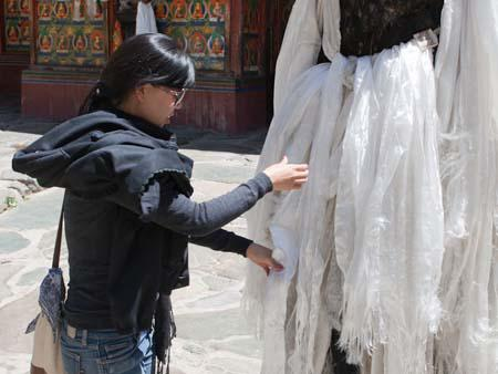 Sonya tying a white scarf to the prayer pole in the courtyard